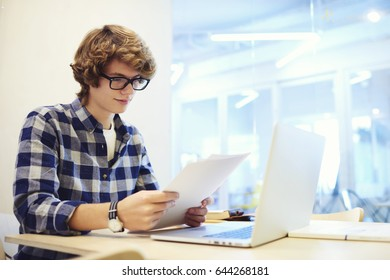 Professional young male project manager of IT corporation reading reports about working process in office sitting near copy space area for advertising, student improving knowledge reading report