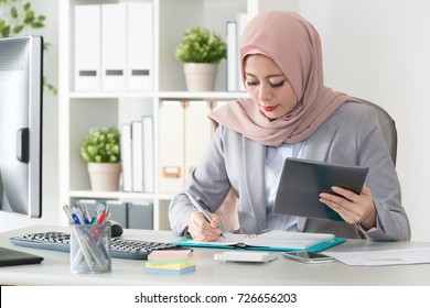 professional young muslim business woman using mobile digital tablet computer work and writing work plan on personal notebook.