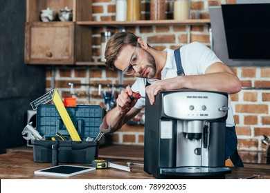 professional young repairman in eyeglasses fixing coffee machine