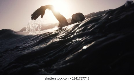 professional young swimmer athlete doing morning swimming freestyle practice at sunrise in open sea. vintage film stylized