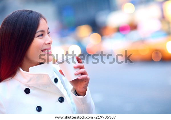 Professional young urban casual business woman in New York City Manhattan drinking coffee walking in street wearing coat downtown with yellow taxi cabs in background.