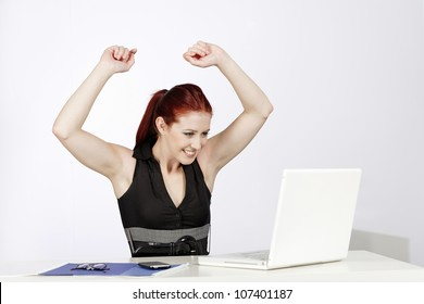 Professional young woman celebrating at work in her office