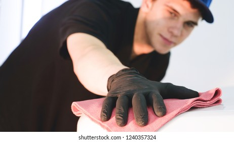 Professional young worker guy (man) polishes (wipes) the body of transport using a rag. Concept from: Cereful work, After polishing, Refreshment, Finished.