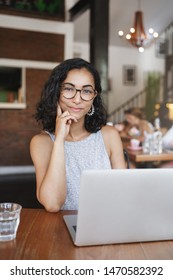 Professionalism, freelance and digital-nomad concept. Vertical shot pretty female entrepreneur working in co-working cafe, sit coffee table near opened laptop, working on project outside office