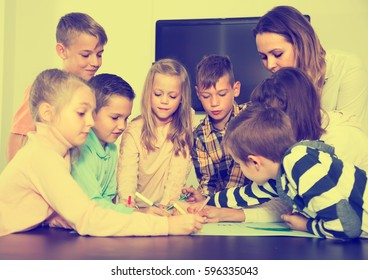Professor and elementary age children drawing together one picture in classroom