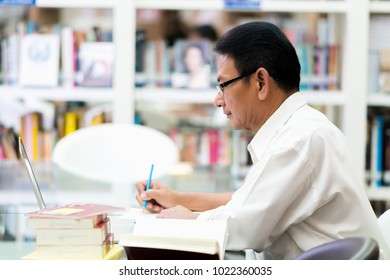 The professor is searching for knowledge with laptop in the library.