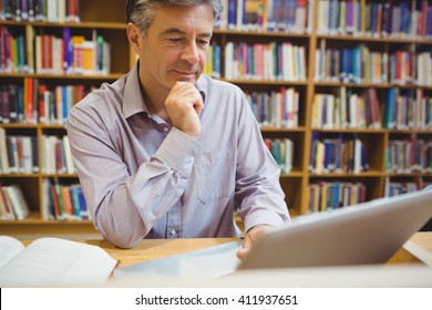Professor sitting at desk using laptop in college library