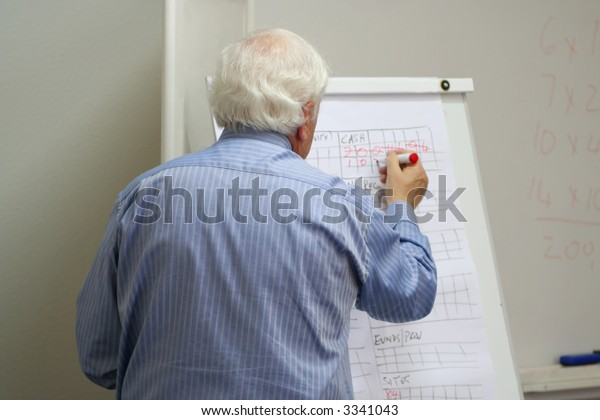 Professor writes on the blackboard in the MBA class