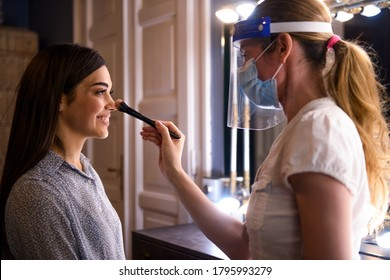 Proffesional adding make up to a beautiful models face.