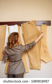 Proffesional Female Tailor choosing clothing paper pattern for new suit at modern atelier