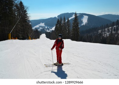 Proffesional winter sport competition on resort in Ukraine. Skier in red ski suit costume on mountain slope on snow mountain background. Vertical portrait of skier-woman.