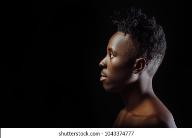 profile of African American man with dreadlocks on black background.