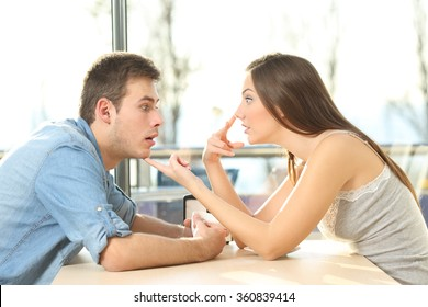 Profile of an amazed casual man looking at cleavage of annoyed girl who is saying him look me in the eyes during a date in a coffee shop