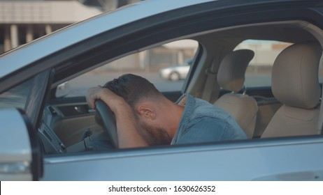 Profile of annoyed male driver sitting in the car talking by phone. Young man calling car support services shouting on smartphone. Car trouble.