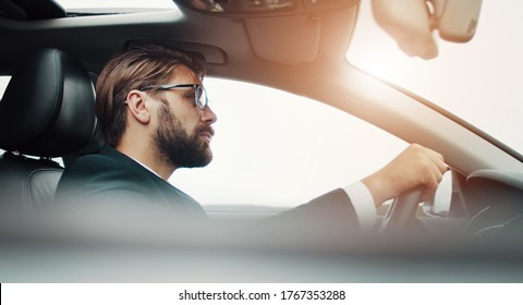 Profile of attentive businessman sitting behind wheel driving car