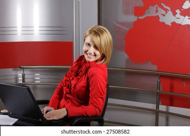 profile of attractive journalist and presenter in front of the laptop looking at the camera in a television studio