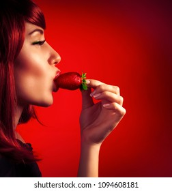 Profile of an attractive woman bites strawberry isolated on red background, closing eyes of pleasure, passion and seduction concept