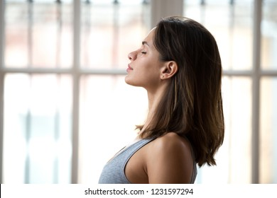 Profile attractive young woman standing with closed eyes near window dreaming breathing fresh air thinking feels calmness and appeasement. Side view female wearing sportswear ready for yoga classes