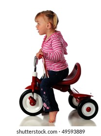 Profile of a barefoot two year old riding a little red tricycle.  Isolated on white.