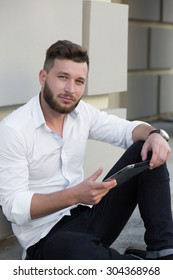 Profile of bearded handsome man freelancer working on tablet PC. Serious man sitting near building with tablet pc.