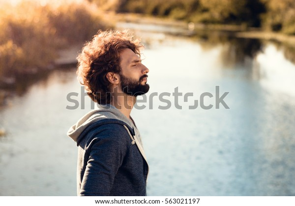 Profile of bearded man on river background. Young guy enjoying breathing fresh air, standing on water bank. Rest, relax, pleasure, nature concept