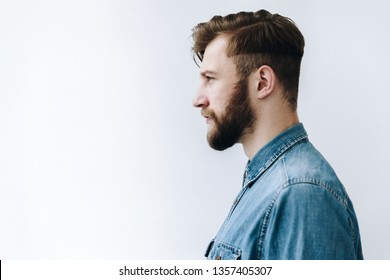 Profile bearded Man portrait. Side view of young blond guy in jean shirt looking forward, on the white background