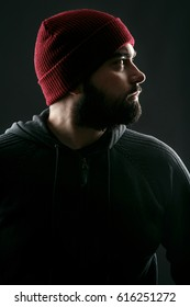 Profile of bearded young man in red hat standing on grey background
