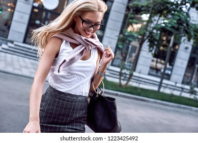 Profile of a beautiful businesswoman with glasses and handbag. She crosses the road and smiling