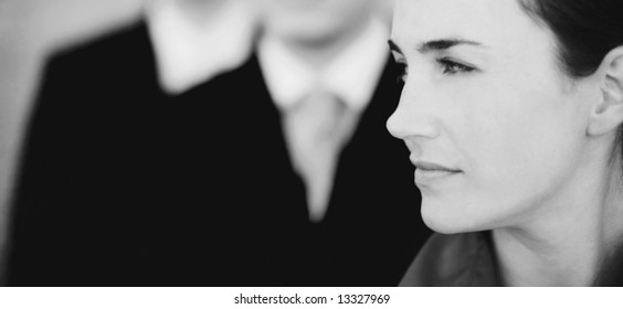 profile of beautiful businesswoman with two businessmen in the background