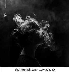 profile of a beautiful girl on a black background. The face of a girl exhaling smoke. Smoking redhead woman. Head in hookah smoke