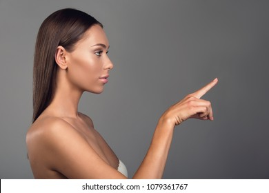 Profile of beautiful girl touching something pleasant with her finger. Copy space in right side. Isolated on background