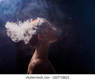 profile of a beautiful naked girl on a black background. The face of a girl exhaling smoke. Smoking redhead woman. Head in hookah smoke