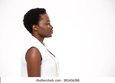 Profile of beautiful serious african american young woman with short haircut over white background