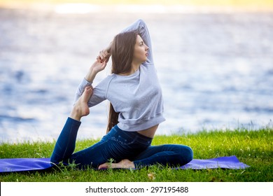 Profile of beautiful sporty young woman working out on city street, doing warming up stretching exercises on lake in park, sitting in Eka Pada Rajakapotasana, full length