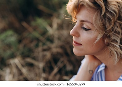 Profile of a beautiful woman with curly hair in a summer wheat field at sunset. Soft selective focus. .