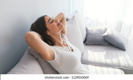Profile of a beautiful woman relaxing lying on a couch at home. Portrait of a girl relaxing on a sofa after work at home sitting on a sofa in the living room at home