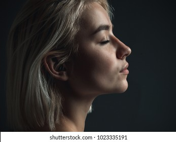 A profile of a  beautiful young blond woman.