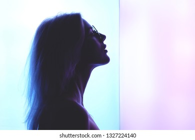 Profile of a beautiful young blond woman with glasses against a background of blue pink creative neon lighting