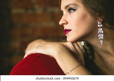Profile of a beautiful young blue-eyed girl with earrings on a brick wall background