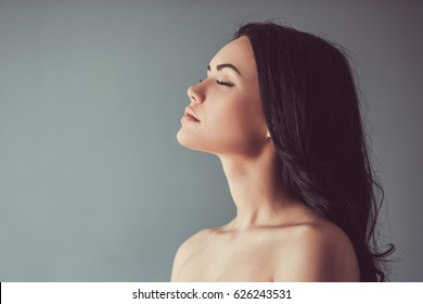 Profile of beautiful young brunette with bare shoulders and closed eyes, on gray background
