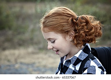Profile of Beautiful young girl with red hair outdoors in Autumn season