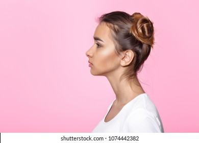 Profile of beautiful young woman on pink background