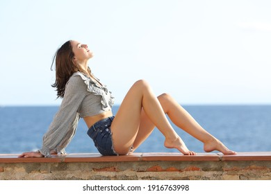 Profile of a beauty woman with perfect waxed legs sitting breathing fresh air on the beach