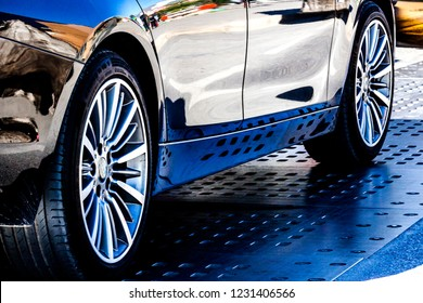 Profile of a black sport high performance car on the street: wide tires and beautiful shiny reflections  - Shutterstock ID 1231406566