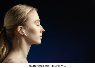 profile of blonde young woman with bluetooth earphones and closed eyes on dark blue background