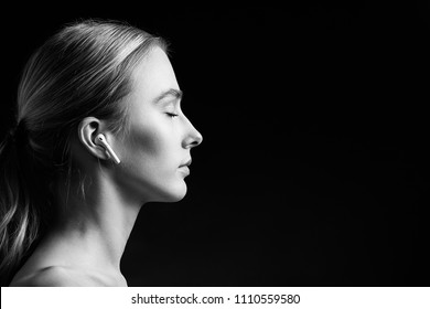profile of blonde young woman with bluetooth earphones and closed eyes on black background, monochrome