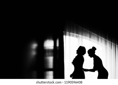 Profile of the bride and her friend who lacing corset in a wedding dress near the window on a black and white photo