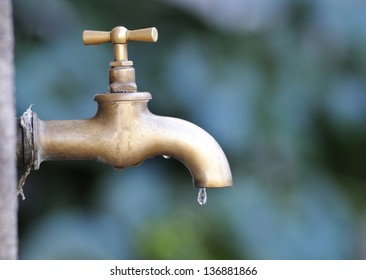profile of a bronze metallic faucet with water drop