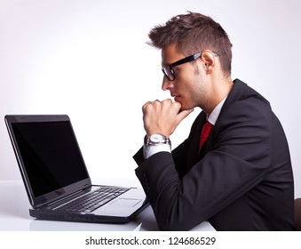 Profile of business man sitting at desk working on laptop computer