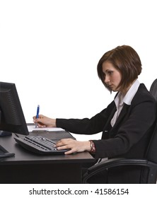 Profile of a businesswoman taking notes at her desk.